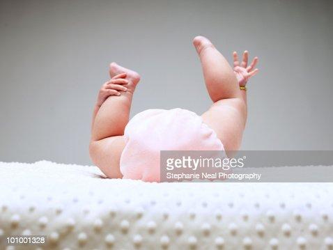 Close up of baby grabbing feet : Stockfoto