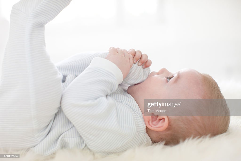 Close up of baby laying on rug : Stock Photo