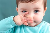 Close up of a baby girl looking at camera with a big blue eyes with a green unfocused background