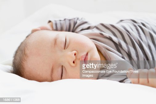 Close up of baby sleeping on bed : Stock Photo
