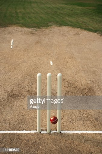 Close up of ball hitting cricket stumps, Bails coming off