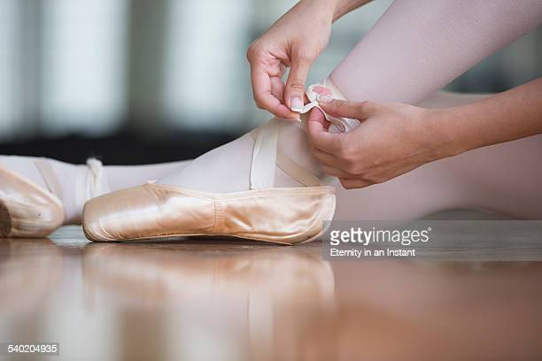 Close up of ballerina putting on her shoes.