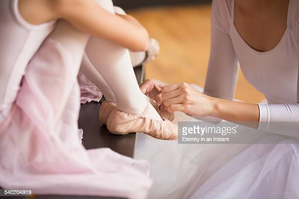 Close up of ballet teacher helping her students