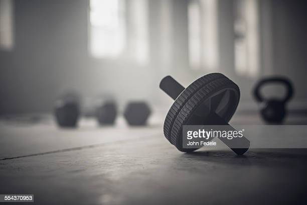 Close up of barbell weights on floor of dark gym