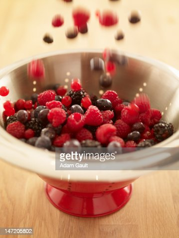 Close up of berries falling into red colander : Foto de stock