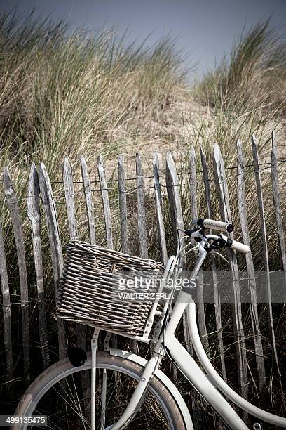 Close up of bicycle against sand dune fence, Vollendam, Netherlands
