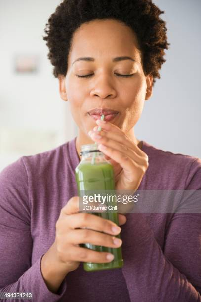 Close up of Black woman drinking green smoothie