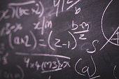 Close up of blackboard with maths equations and sums Vintage Retro Filter.