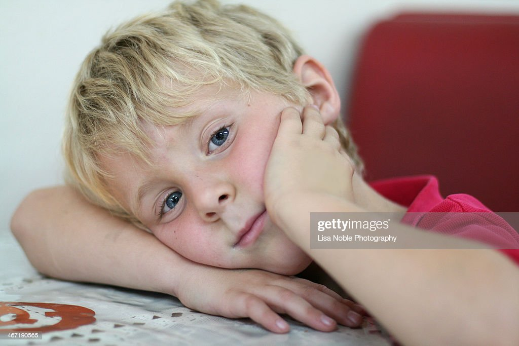 Close up of blond boy with head resting on arm : Stock Photo