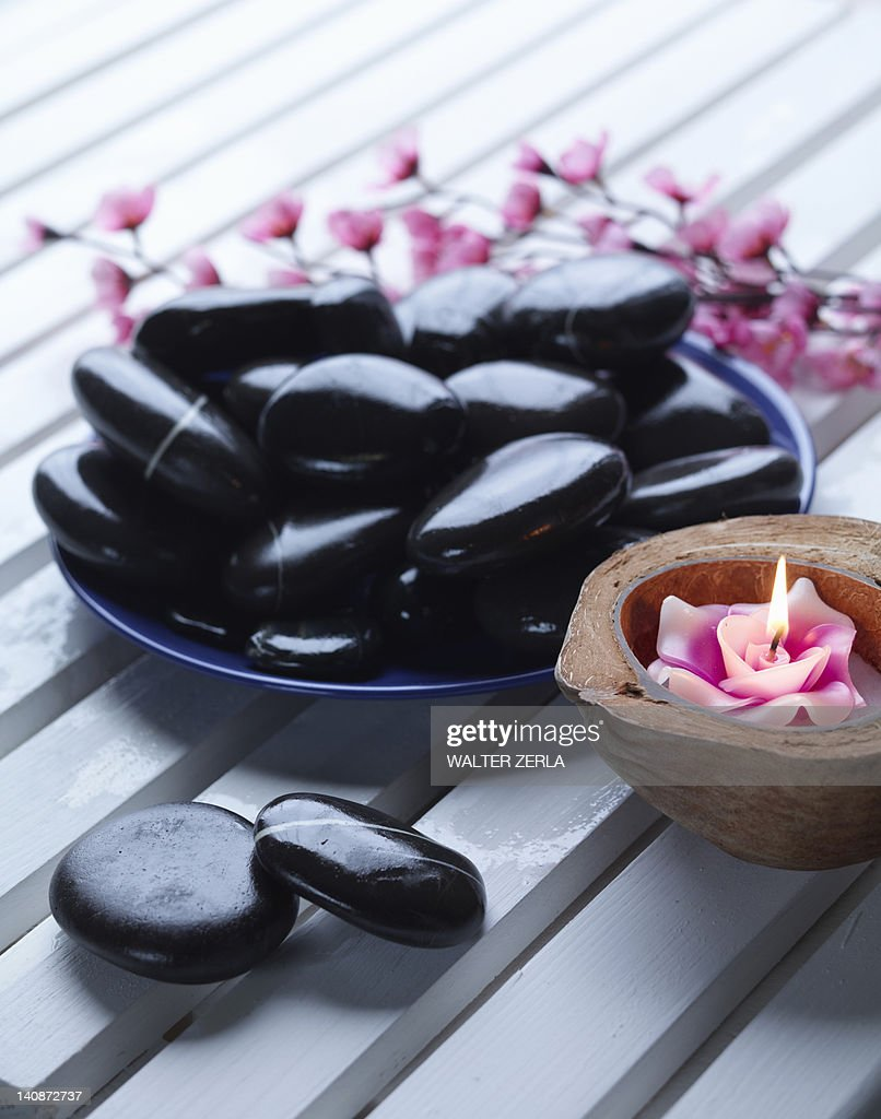 Close up of bowl of rocks and candle : Stock Photo