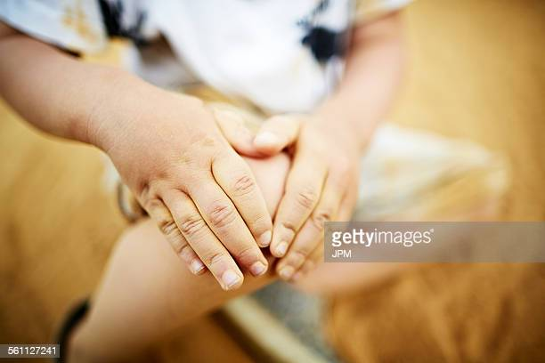 Close up of boy holding his knee with his hands