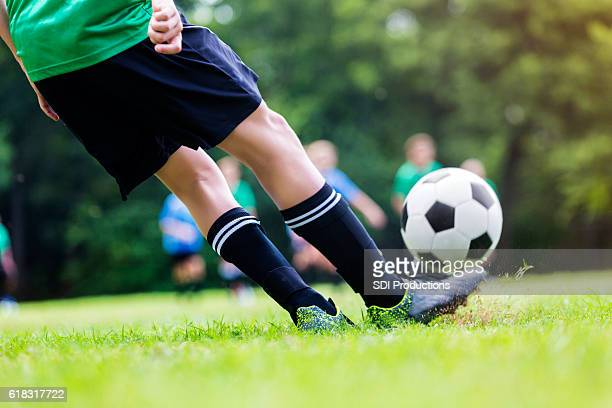 Close up of boy kicking soccer ball during game