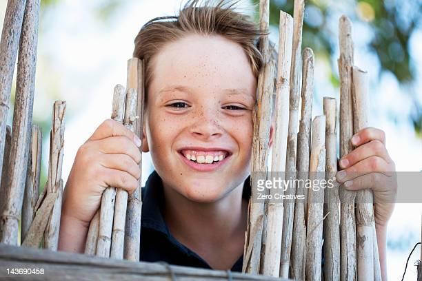 Close up of boy smiling behind fence