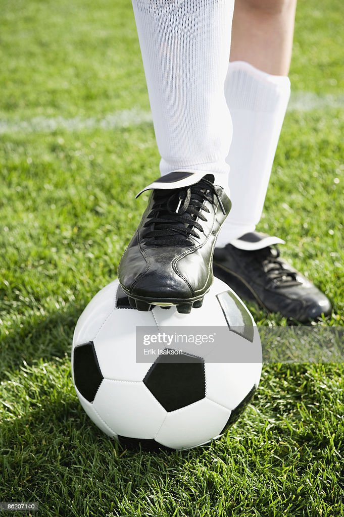 Close up of boy's foot on soccer ball : Stock Photo