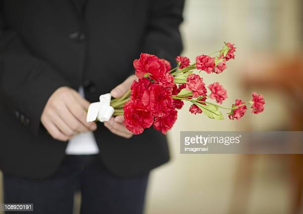 Close up of boys hands holding a carnation flower