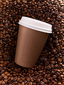Close up of brown coffee cup on top of coffee beans