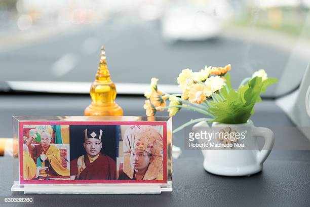 Close up of Buddhist religious accessories on car dashboard The blurry background highlights them even more