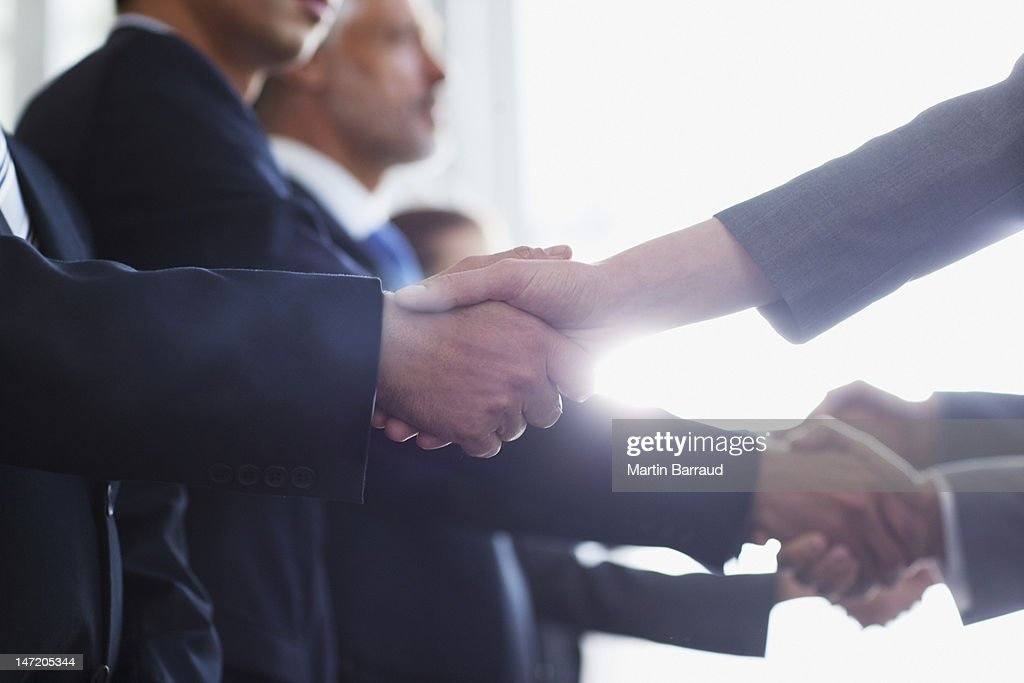 Close up of business people shaking hands in a row