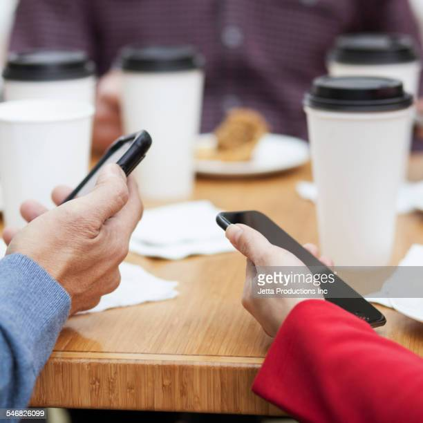 Close up of business people using cell phones at working breakfast