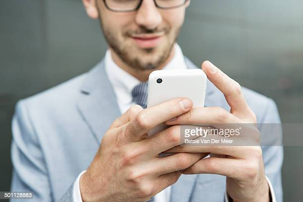close up of businessman holding mobile phone.