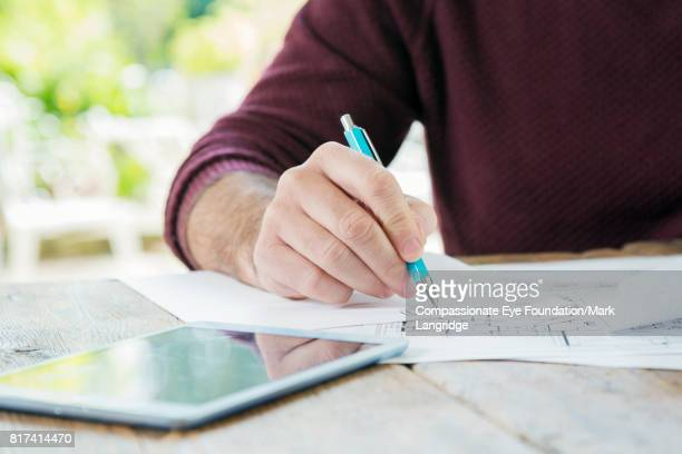 Close up of businessman in kitchen with paperwork and digital tablet