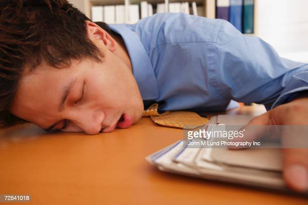 Close up of businessman sleeping on desk
