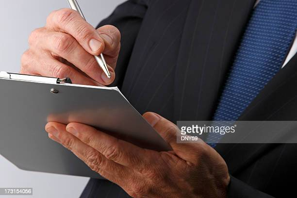 Close up of businessman writing clipboard