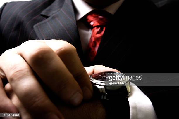 Close up of businessman's hands checking the time on watch