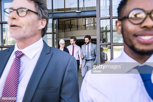 Close up of businessmen leaving office building