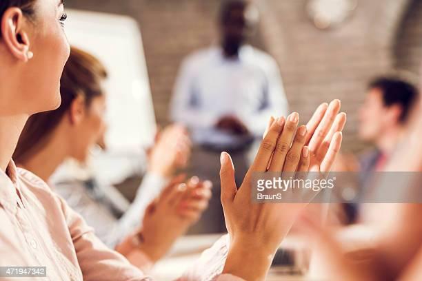 Plano aproximado de mulher de negócios aplaudir o seu colega em boa apresentação.