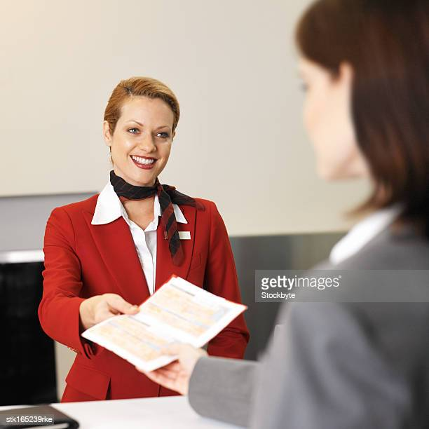close up of businesswoman checking in and stewardess checking ticket