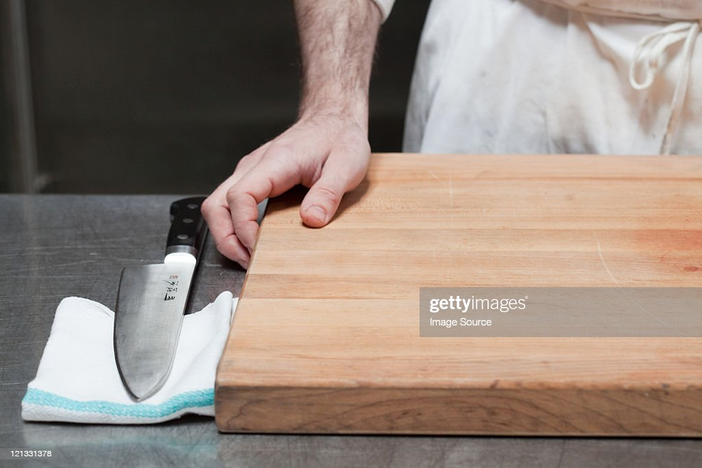 Close up of butcher with chopping board and knife : Stock Photo