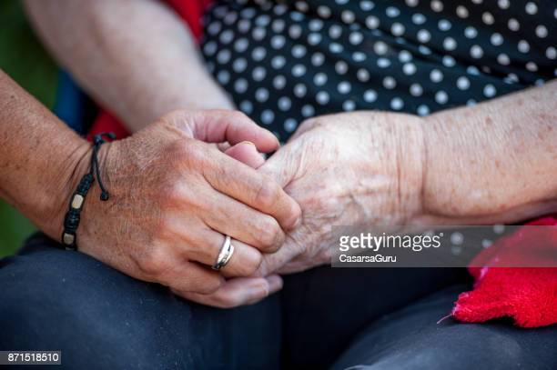 Close Up Of Caretaker Hands Holding Senior Woman Hands