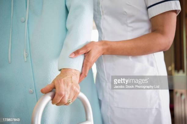 Close up of caretaker helping older woman use walker