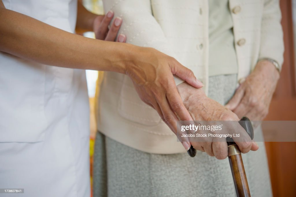 Close up of caretaker helping older woman walk