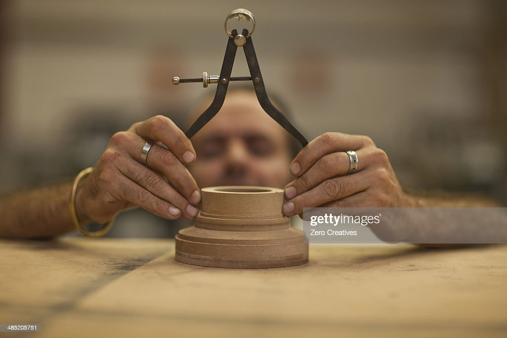 Close up of carpenter measuring turning wood in workshop : Stock Photo