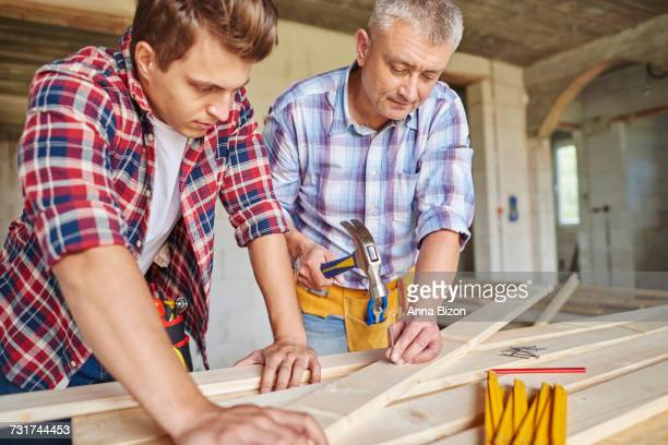 Close up of carpenters with hammer hitting planks. Debica, Poland