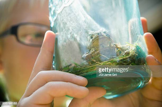 Close up of Caucasian boy holding jar with frog