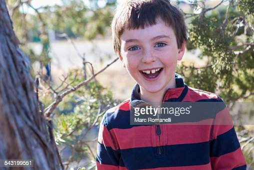 Close up of Caucasian boy smiling near tree