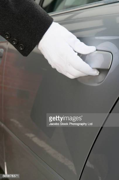 Close up of Caucasian butler opening car door