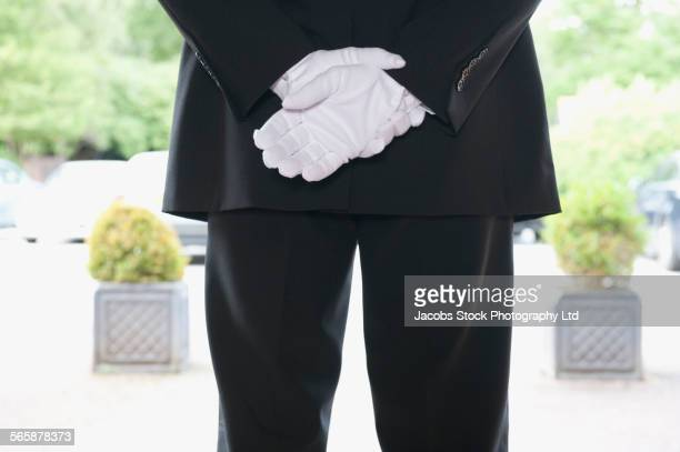 Close up of Caucasian butler waiting at hotel entrance