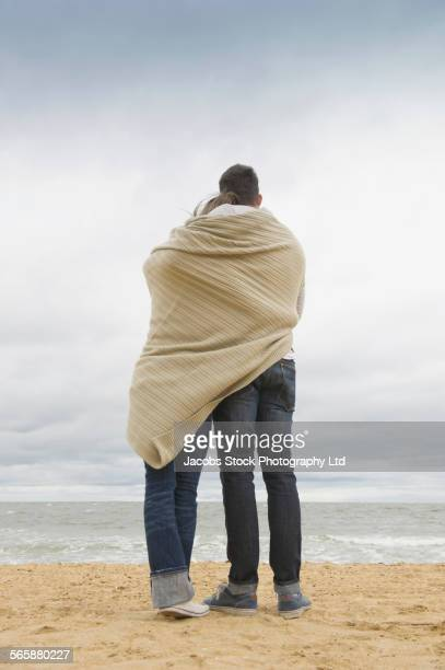 Close up of Caucasian couple hugging on beach