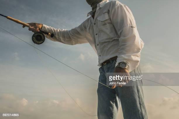 Close up of Caucasian man fishing under blue sky