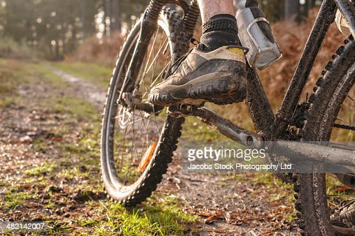 Close up of Caucasian man's muddy foot on mountain bike