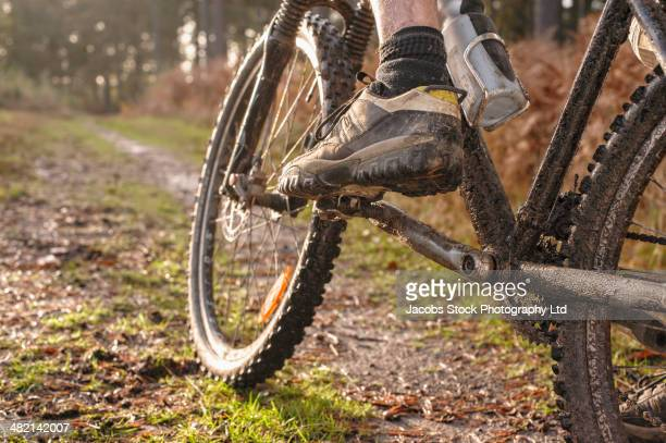 Close up of Caucasian man's muddy foot on mountain bike