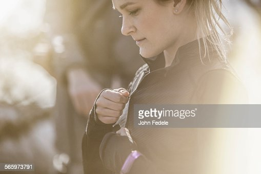 Close up of Caucasian woman zipping jacket