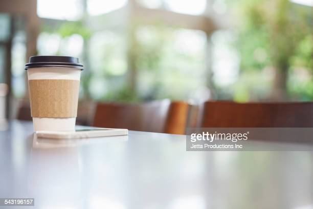 Close up of cell phone and coffee on table