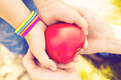 close up of child and mother hands with heart; health care, love, hope and family concept - vintage filter applied