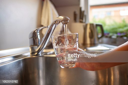 Close up of children hands, pouring glass of fresh water from tap in kitchen : Foto de stock