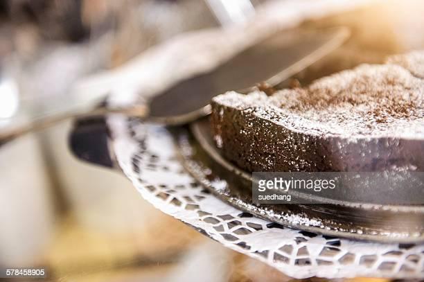 Close up of chocolate cake on doily and cake server